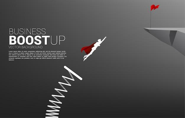 Siluetta dell'uomo d'affari che vola alla bandiera rossa sulla scogliera con trampolino di lancio. banner di spinta e crescita nel business.