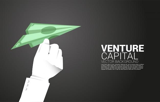 Siluetta dell'aeroplano di carta di origami della banconota della tenuta della mano dell'uomo d'affari. concetto di business di avviare business e imprenditore