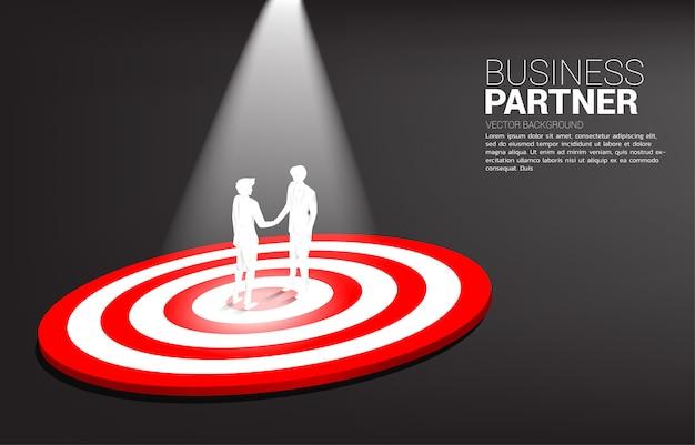 Siluetta della stretta di mano dell'uomo d'affari sul centro del bersaglio. concetto di business di lavoro di squadra e campionato. vincere l'obiettivo di mercato