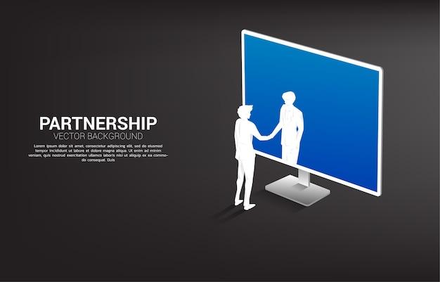 Siluetta della stretta di mano dell'uomo d'affari dal monitor del computer. concetto di partnership commerciale digitale e tecnologia di cooperazione.
