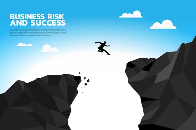 La siluetta dell'uomo d'affari salta alla scogliera più alta.