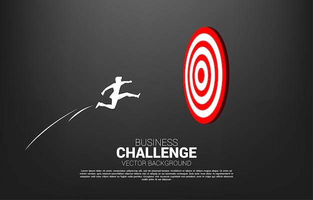 Siluetta dell'uomo d'affari che salta al centro del bersaglio. business concept di targeting e customer.route verso il successo.