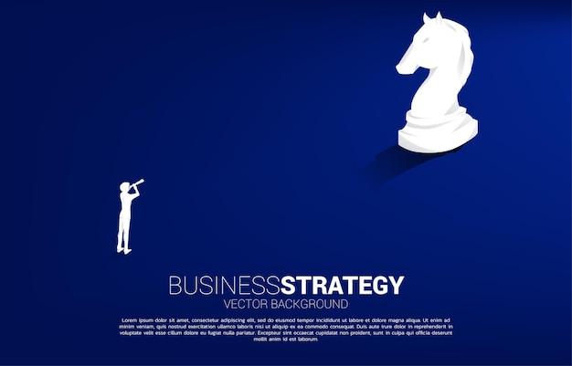 Siluetta dell'uomo d'affari che osserva tramite il telescopio al vettore della siluetta 3d del pezzo degli scacchi del cavaliere. icona per la pianificazione aziendale e il pensiero strategico