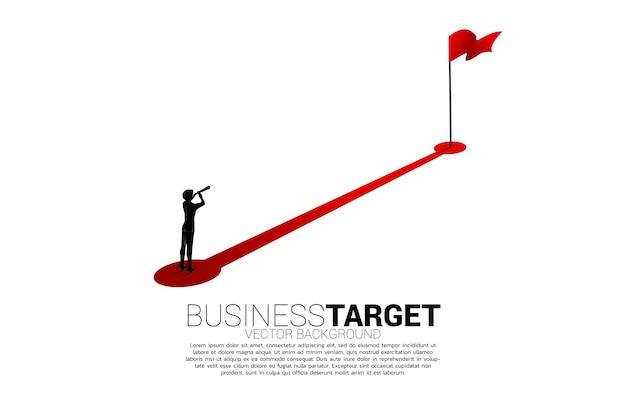 Siluetta dell'uomo d'affari che guarda attraverso il telescopio in piedi sul percorso verso la bandiera rossa all'obiettivo. concetto di persone pronte a iniziare la carriera e gli affari verso il successo.