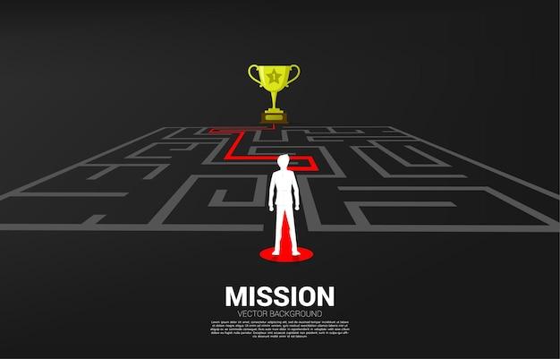 Siluetta dell'uomo d'affari che sta sulla freccia con il percorso del percorso per uscire dal labirinto al trofeo dorato. concetto di business per la soluzione dei problemi e la strategia di soluzione