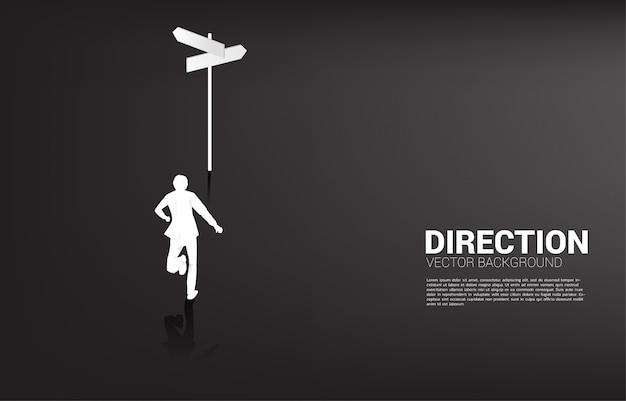 Siluetta dell'uomo d'affari che sta al segnale di direzione. concetto di tempo per prendere una decisione nella direzione degli affari