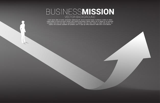 Siluetta dell'uomo d'affari che sta sulla freccia alta. concetto di percorso di carriera e avvio dell'attività