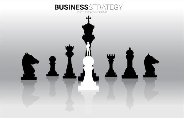 Sagoma di uomo d'affari in piedi sul pezzo degli scacchi pedone bianco davanti a tutto il pezzo degli scacchi nero.