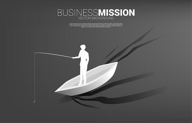 Siluetta dell'uomo d'affari che sta con l'amo da pesca sulla barca. banner di targeting ed esca negli affari.