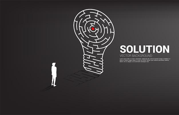Siluetta dell'uomo d'affari che sta con la lampadina dal gioco del labirinto. concetto di business per la risoluzione dei problemi e la ricerca di idee.