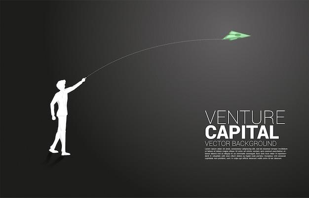 La siluetta dell'uomo d'affari getta l'aeroplano di carta di origami della banconota dei soldi. concetto di business di avviare business e imprenditore