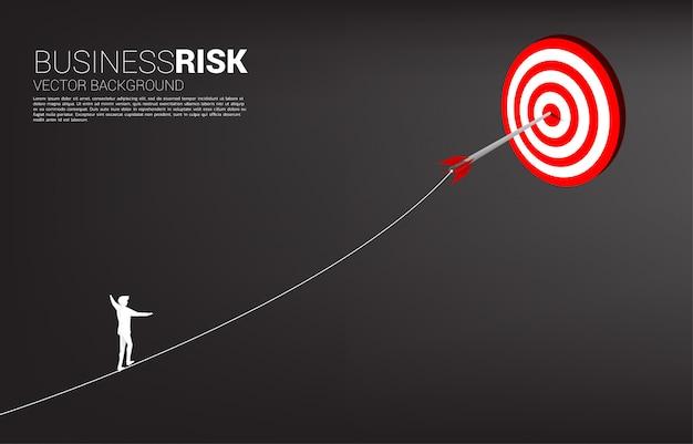 Siluetta della corda della passeggiata dell'uomo d'affari al colpo di tiro con l'arco della freccia sul centro dell'obiettivo. concetto di targeting e sfida aziendale.