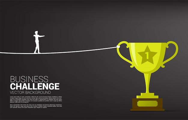 Siluetta della corda della passeggiata dell'uomo d'affari al trofeo dorato. concetto di targeting e business challenge.route to success.