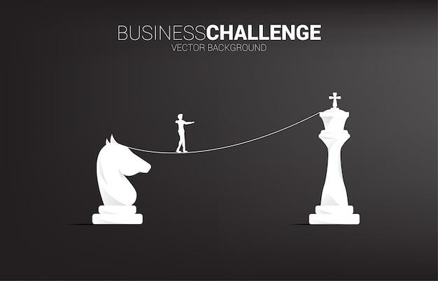 Siluetta dell'uomo d'affari che cammina sul modo della passeggiata della corda a dal cavaliere al re scacchi.