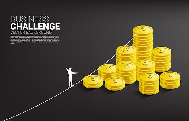 Siluetta dell'uomo d'affari che cammina sul modo della passeggiata della corda al modello dorato della pila della moneta