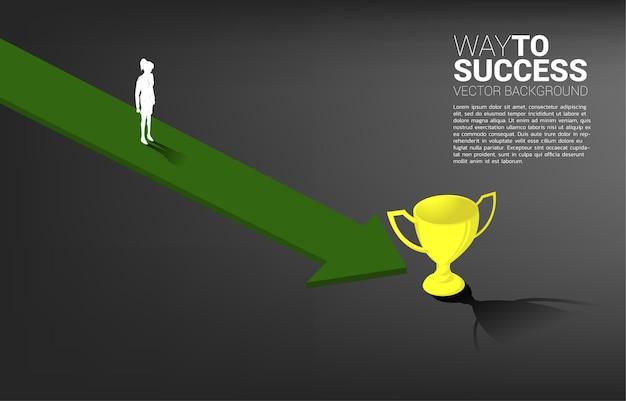 La siluetta della donna di affari sulla freccia si sposta al trofeo dorato. concetto per la direzione aziendale e la visione della missione