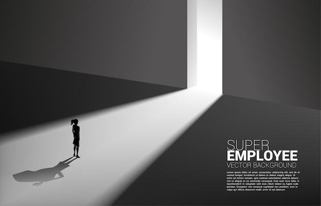 Silhouette di donna d'affari e la sua ombra di supereroe dalla luce del modo di uscita. concetto di potenziamento potenziale e gestione delle risorse umane