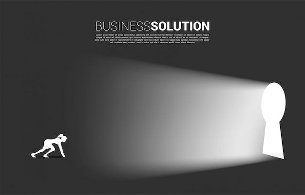 Silhouette di imprenditrice pronta a correre fuori alla porta del buco della serratura.