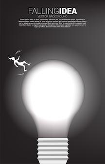 Siluetta della donna di affari scivolare e cadere dalla lampadina. concetto per idea e affari falliti.
