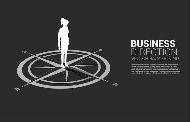 Silhouette di imprenditrice in piedi al centro della bussola sul pavimento.concetto di percorso di carriera e direzione aziendale