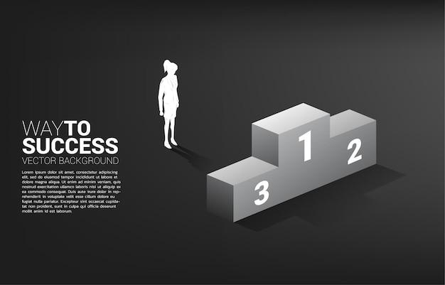 Siluetta della donna di affari che sta con il podio. concetto aziendale di vincitore e successo