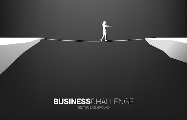 Siluetta della donna di affari che cammina sul modo della camminata della corda. concetto per il rischio d'impresa e la sfida nel percorso di carriera