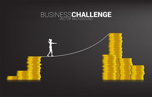 Siluetta della donna di affari che cammina sul modo della passeggiata della corda alla pila dorata della moneta concetto per il rischio di affari e il percorso di carriera