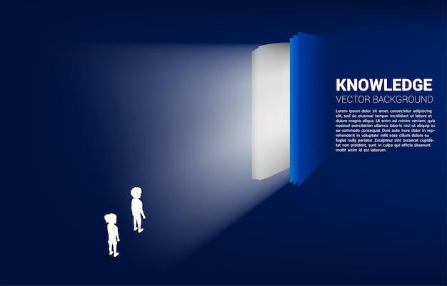 Profili il gruppo di ragazzo e ragazza che stanno con la luce dal libro aperto. concetto di conoscenza del libro
