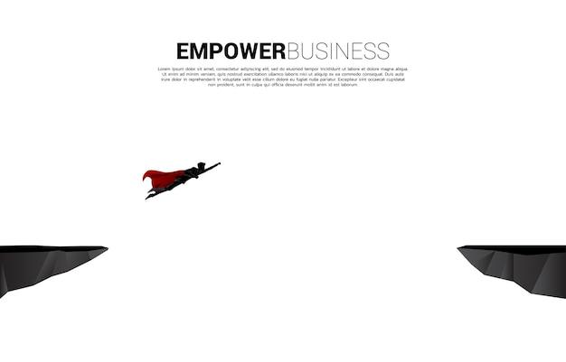La siluetta del supereroe sorvola attraverso l'abisso. concetto di sfida aziendale e responsabilizzazione.