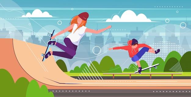 Coppia di pattinatori che eseguono acrobazie nel parco pubblico di skateboard con varie rampe per lo skateboard mix race guy girl adolescenti