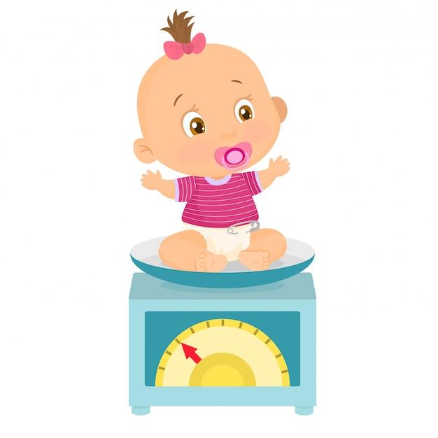 Il bambino piccolo pesava su una bilancia
