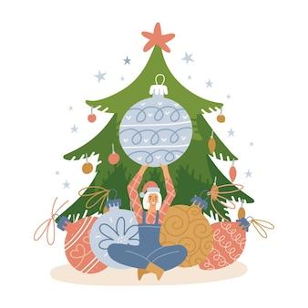 Personaggio di piccola donna che decora l'albero di natale con un grande albero di natale giocattoli ragazza seduta che tiene ...