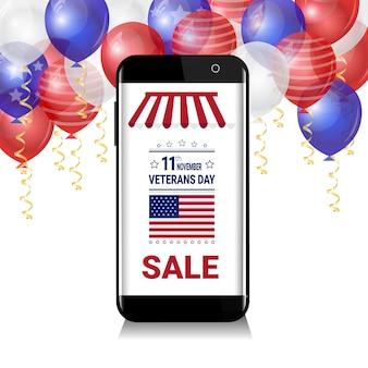 Smartphone con vendita per veteran day messaggio sopra palloncini bianchi, blu e rossi su sfondo