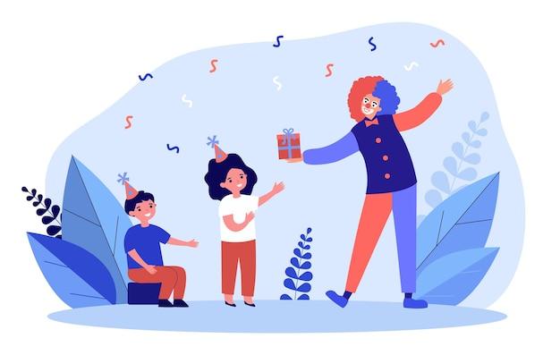 Pagliaccio sorridente che si congratula con due bambini felici con il compleanno. persona comica felicissima che si diverte a salutare i bambini che presenta una confezione regalo. illustrazione vettoriale piatto. anniversario.