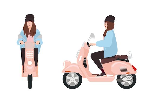 Sorridente ragazza hipster vestita in abiti casual alla moda in sella a scooter rosa.