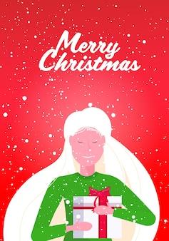 Donna sorridente azienda confezione regalo avvolto buon natale felice anno nuovo vacanze invernali celebrazione concetto verticale