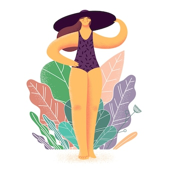 Sorridente giovane donna vestita in costume da bagno e cappello sulla spiaggia.
