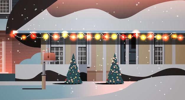 Cortile innevato della casa di notte nella costruzione domestica di stagione invernale con le decorazioni per l'illustrazione orizzontale di vettore di celebrazione del nuovo anno e di natale