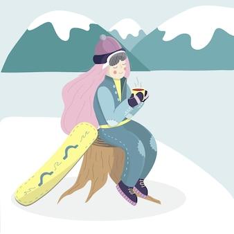 La donna dello snowboarder si riposa e beve il tè caldo