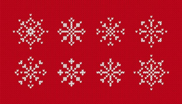 Fiocchi di neve sul motivo a maglia. vettore. set di simboli invernali di natale su sfondo rosso senza soluzione di continuità