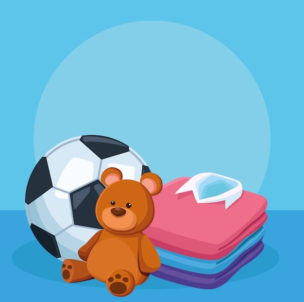 Pallone da calcio, orso e camicie da uomo impilate sul blu