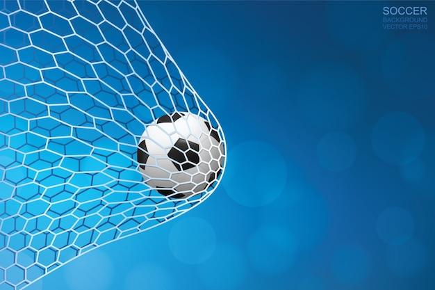 Pallone da calcio in rete con luce offuscata bokeh sfondo.