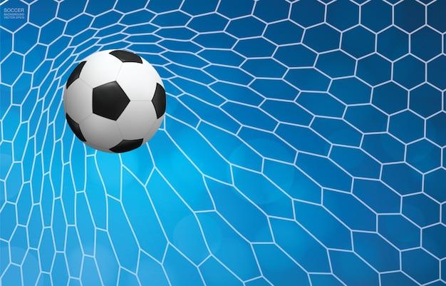 Pallone da calcio e rete da calcio con il fondo del bokeh della sfuocatura.