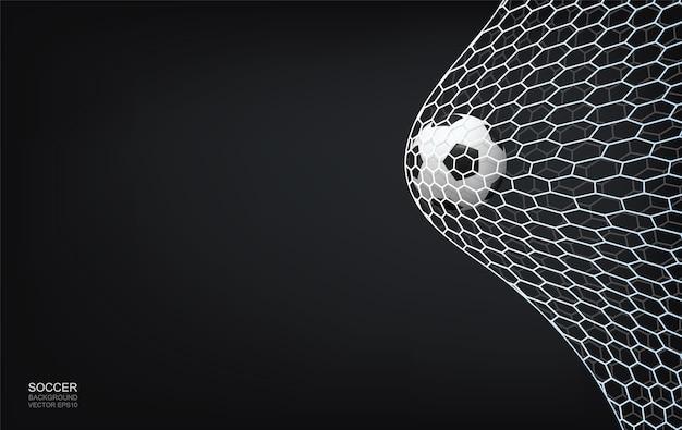 Pallone da calcio e rete da calcio su sfondo scuro con area per lo spazio della copia.