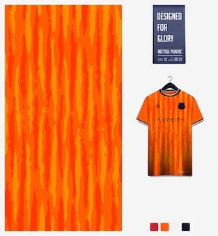 Disegno del modello del tessuto della maglia da calcio modello astratto su sfondo arancione