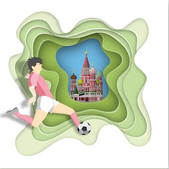Il calciatore dà dei calci alla palla sul fondo di mosca