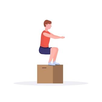 L'uomo di sport che fa il box squat esercita il tipo che salta risolvendo nel fondo sano di bianco di concetto di stile di vita del crossfit della palestra