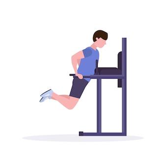Uomo di sport che fa le esercitazioni sul tipo della barra parallela che risolve nel crossfit della palestra che prepara il fondo sano di bianco di concetto di stile di vita