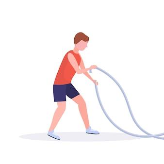 L'uomo sportivo che fa il crossfit si esercita con l'addestramento del tipo della corda di battaglia nel fondo bianco di concetto sano di stile di vita di allenamento cardio della palestra integrale
