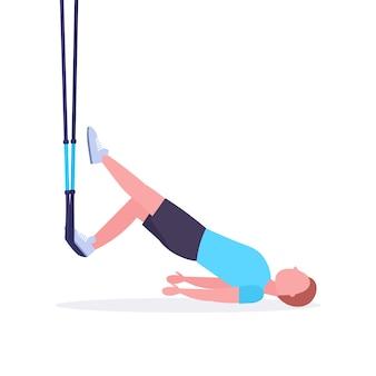 Uomo sportivo che fa esercizi con sospensione fitness cinghie elastico tipo tirante in palestra crossfit cardio allenamento sano stile di vita concetto sfondo bianco integrale
